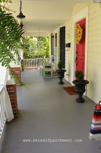grey cottage porch with white railing and red door