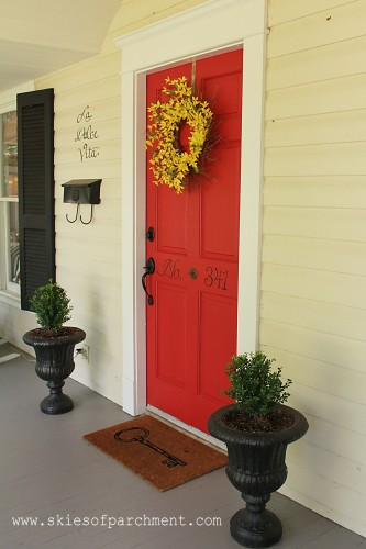 red front door with planters